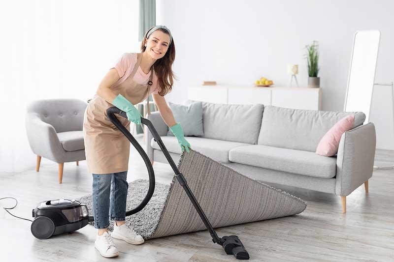 Woman vacuuming lounge room