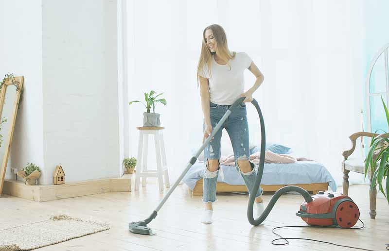 A woman vacuuming her floor at home.